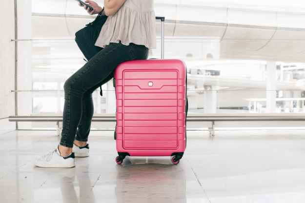 woman in white top and denim jeans sitting on red luggage bag